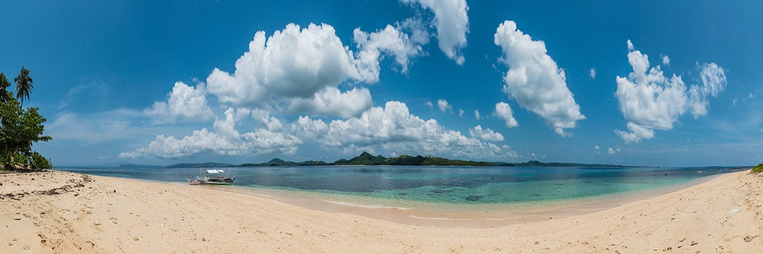 Island life at Siargao: white sand beach of Casulian island with clear water and cloudy sky