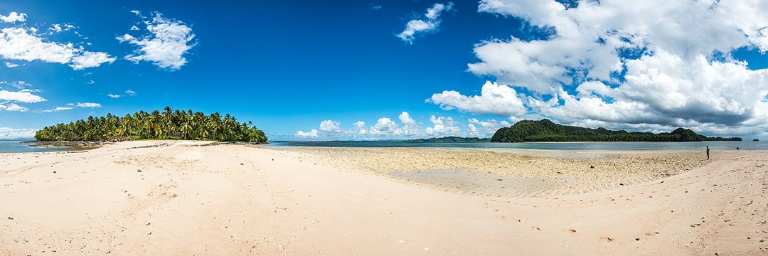 Island life at Siargao: Cowhagan island with white sand beach, clear waters, palm trees and cloudy skies