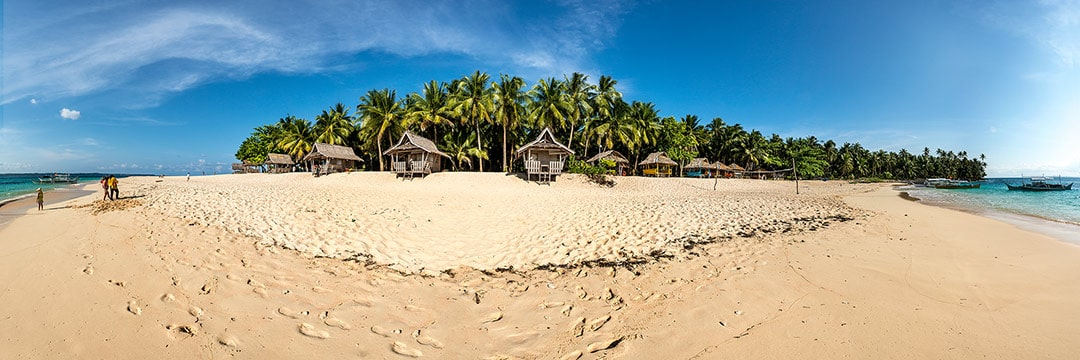 Island life at Siargao: Daku island with several several shelters for hire on white sand beach