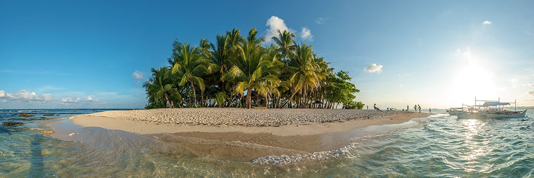 Island life at Siargao: Small deserted island Guyam decorated with palm trees and surrounded by white sand