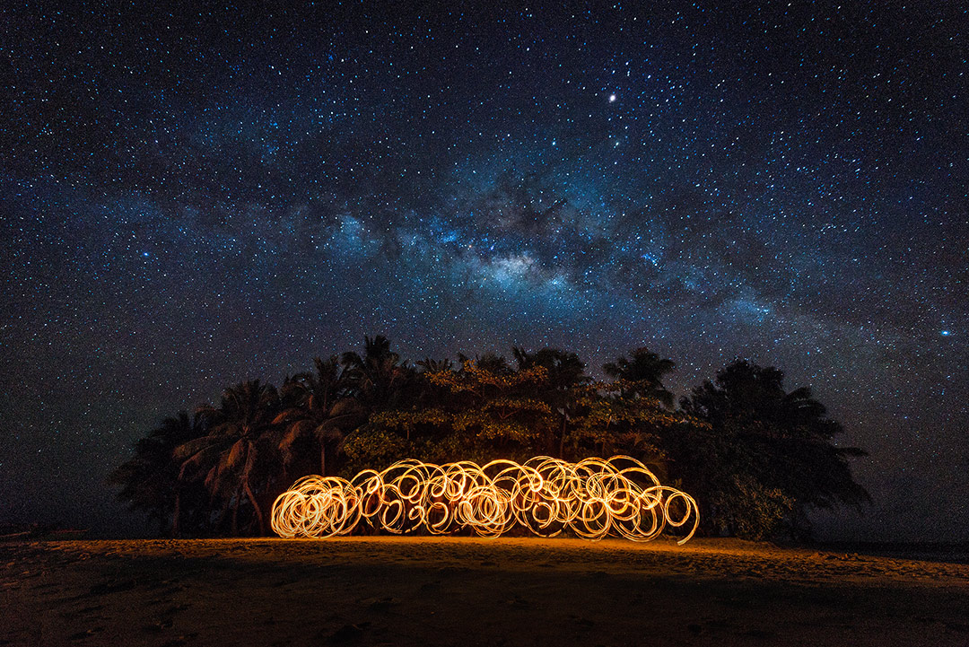 Fire dancer on Guyam island with milky way in background