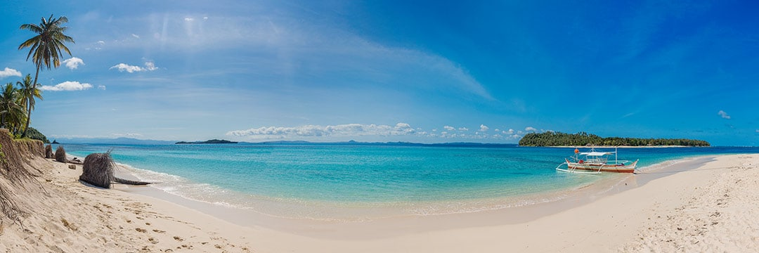 Island life at Siargao: La Janusa island white sand beach with clear blue water and blue sky