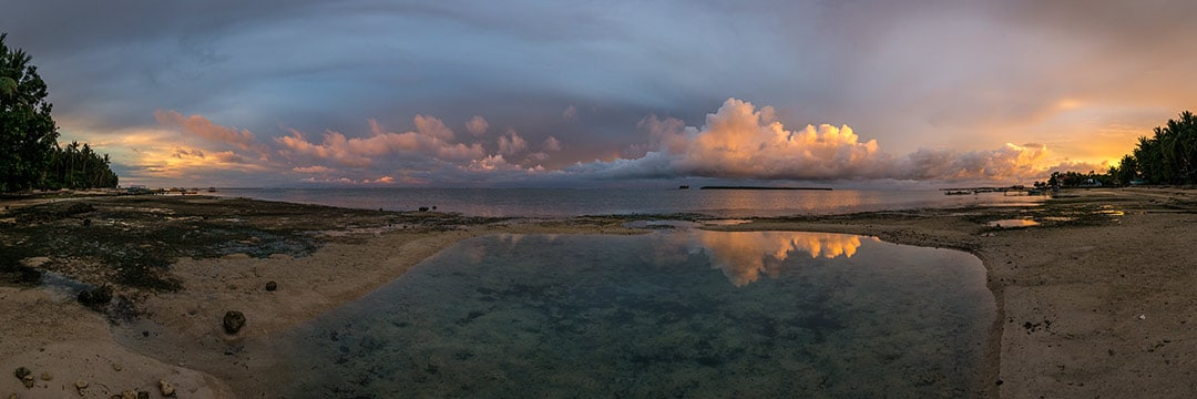 Island life at Siargao: Colourful sunset on the beach with dramatic clouds and reflections in the water