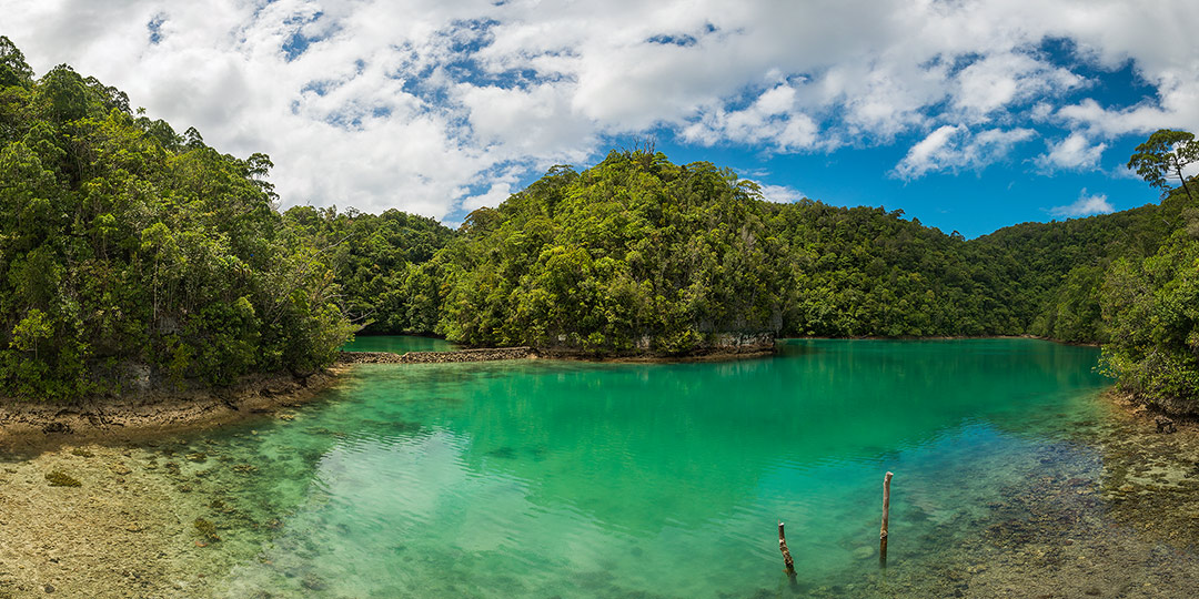 Island life at Siargao: Sugba lagoon near Siargao with turquoise coloured water, green vegetation and blue sky with clouds